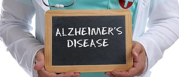 Medical doctor holding a chalk board with the words Alzheimer's disease.