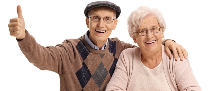Senior man and woman smiling and giving thumbs up.