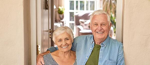 Elderly couple standing in a hallway smiling.