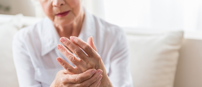 Older woman holding her hands in pain.