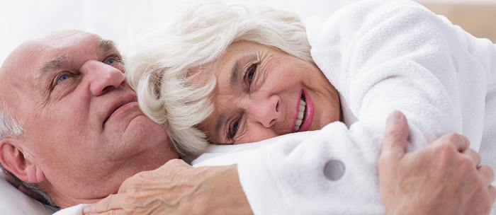 Elderly couple lying down holding each other.